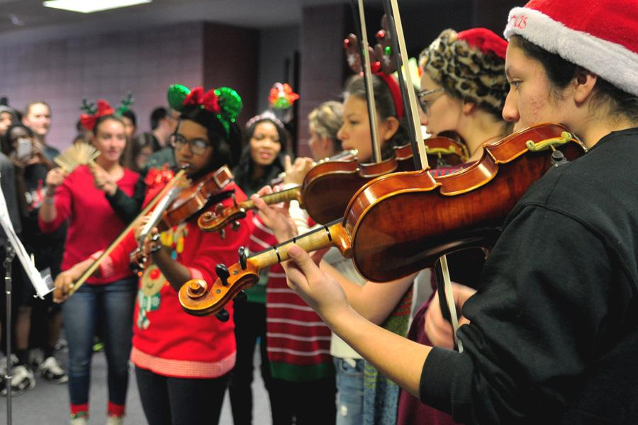 Students bring sheet music and instruments with them when they sing to classes.