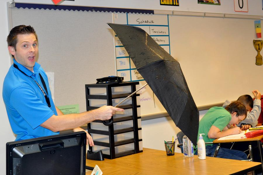 "Former meteorologist Chad Garneau teaches his students math while holding an umbrella. ""I decided to become a math teacher because I wanted to give back to the community by teaching kids the language of science, which is math,"" Garneau said."