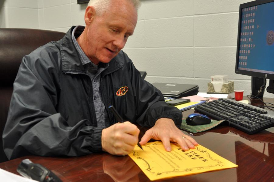 Principal Randy Kirk signs the Top Tiger Award certificates for the January winners.