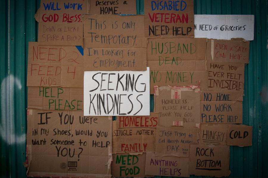 A collection of cardboard signs that identify some of the struggles of living poverty.