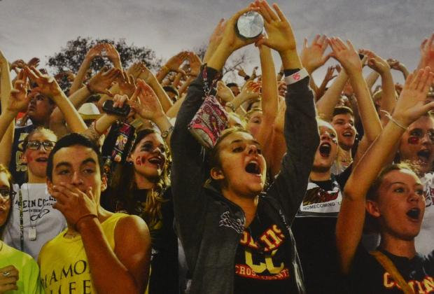 Students cheer for the football team during kickoff.