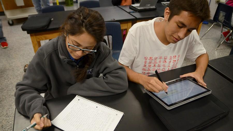 Senior Mavi Ontiveros and Tristan Ortega take notes on their preferred device, the computer and paper.