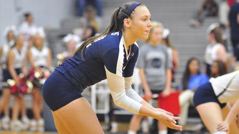 Senior Kelly Farina prepares to receive the ball during a varsity volleyball game.