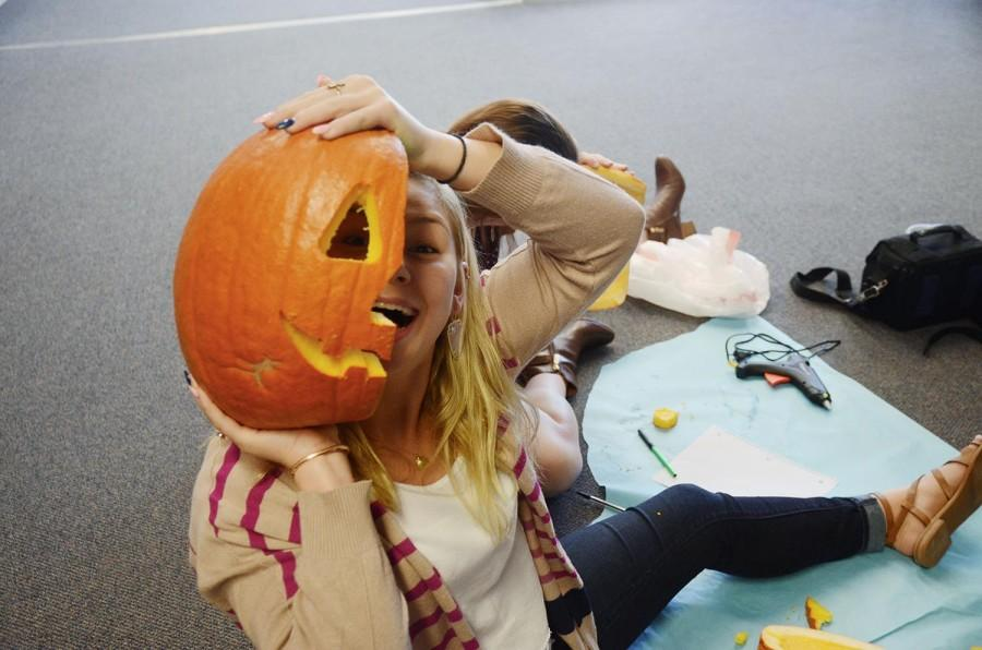 Student council member senior Brianna Zuckero displays her half-finished pumpkin