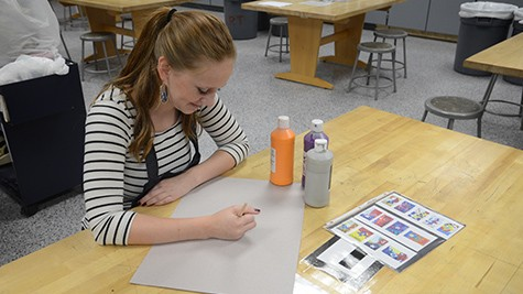 Meliya Leavitt sketches an outline for her artwork before painting it in.