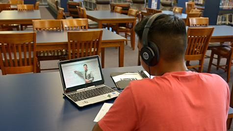 Junior Gabriel Gomez watches a lesson in the library at his own pace, a benefit of blended classes.