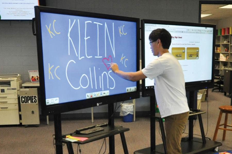 "While using the new library technology, senior Kevin Huang doodles a heart. ""I like the new technology because it is more interactive and visual,"" Huang said."