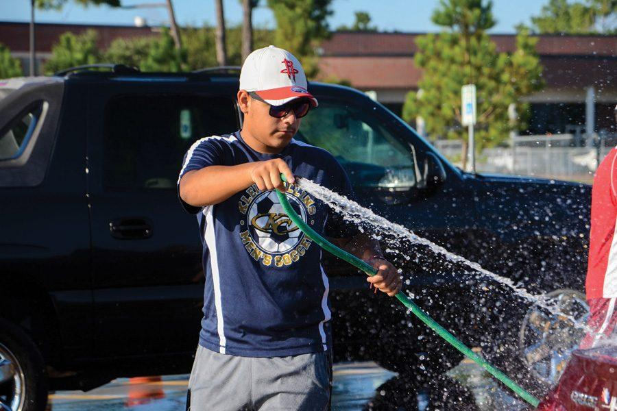Junior+Anthony+Lopez+washes+a+car+for+the+annual+soccer+fundraiser.+%241%2C800+was+raised.