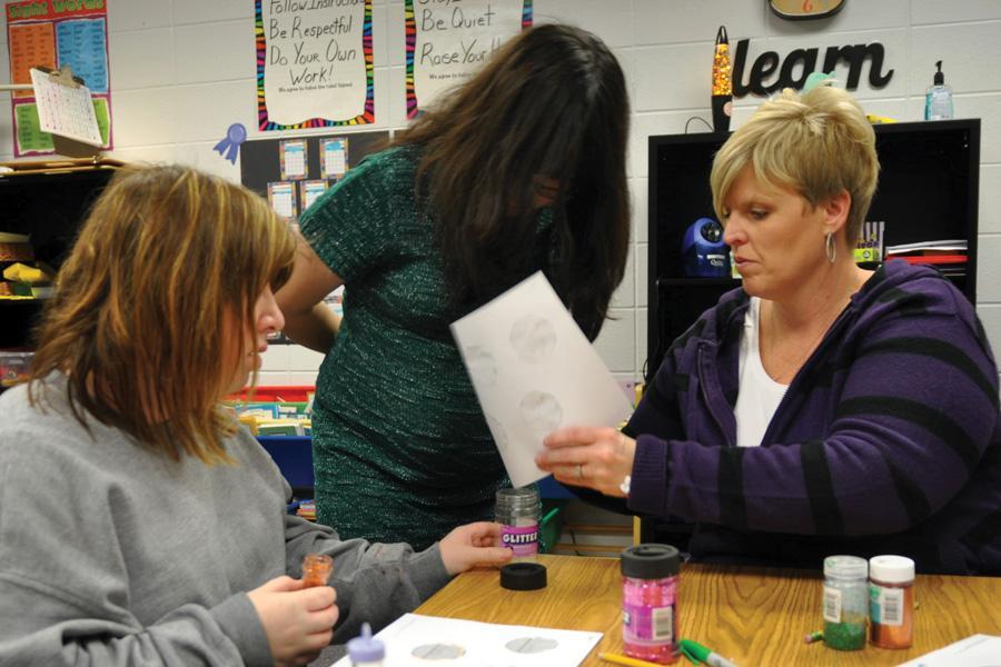 Helping a special needs student, special education teacher Tamara Wiltz explains a Christmas craft project.