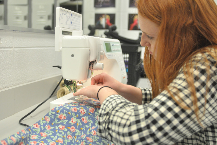 """Using a sewing machine, senior Caroline Hendricks practices her skills. """"I love costuming,"""" Hendricks said. """"It allows me to open up my creativity to different time periods."""""""