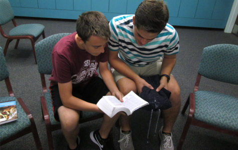Sophomore Ryan Del Papa and junior Scott Brighton read from the scriptures before seminary starts.