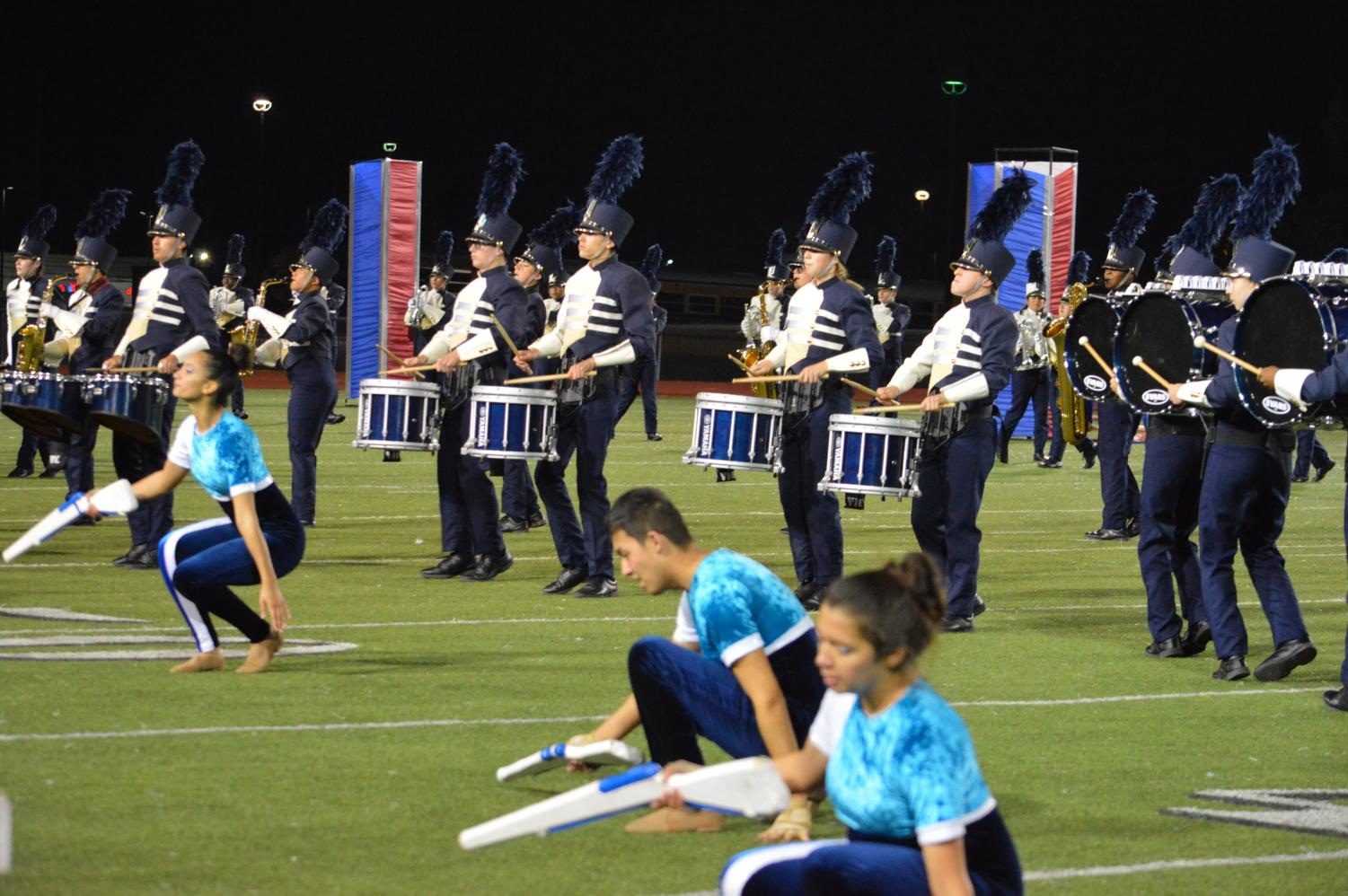 The colorguard, drumline, and band preform their show at a football game.