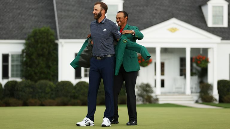 Last year's winner, Tiger Woods, placed the coveted green jacket on Johnson.
