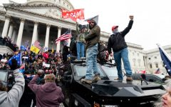 A violent mob of Trump supporters stand on the U.S. Capitol Police armored vehicle as others take over the steps of the Capitol on Wednesday, Jan. 6, 2021, as the Congress works to certify the electoral college votes.