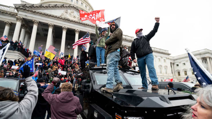 A+violent+mob+of+Trump+supporters+stand+on+the+U.S.+Capitol+Police+armored+vehicle+as+others+take+over+the+steps+of+the+Capitol+on+Wednesday%2C+Jan.+6%2C+2021%2C+as+the+Congress+works+to+certify+the+electoral+college+votes.