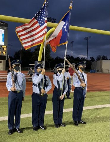 Cadets Hunter Knutson, Victor Tamez, Olivia Garcia and Terrell Wallace holding flags on the football field.