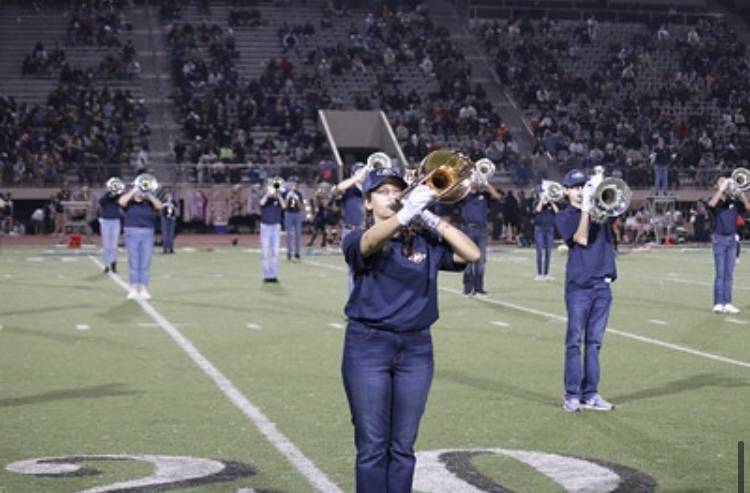 Band+students+line+up+on+the+field+during+a+football+game+on+November+19%2C+2020.+