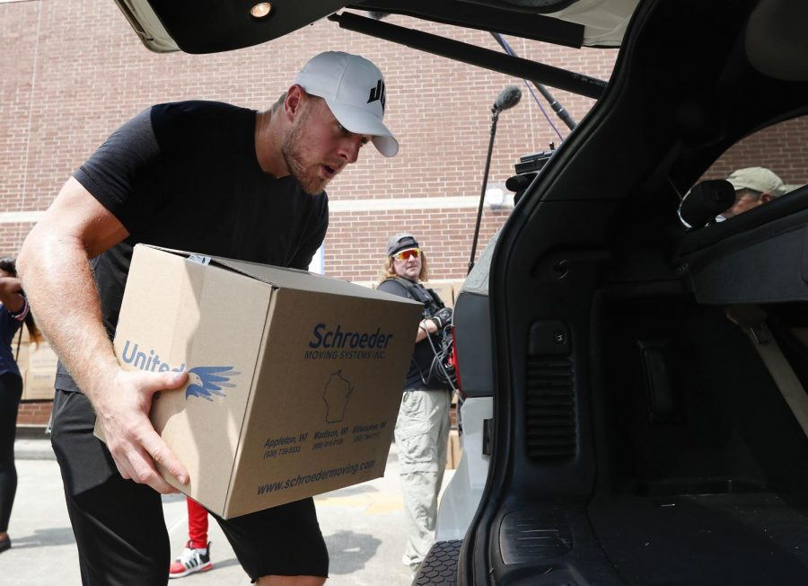 J.J. Watt, pictured above, places a box of relief supplies in the back of a vehicle on Monday, Aug. 27 2017 (Brett Coomer/Houston Chronicle via AP, Pool)