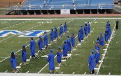 Seniors gathered at an outdoor graduation on a football field.