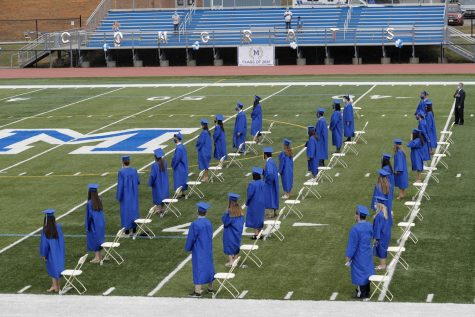 Seniors gathered at an outdoor graduation on a football field.